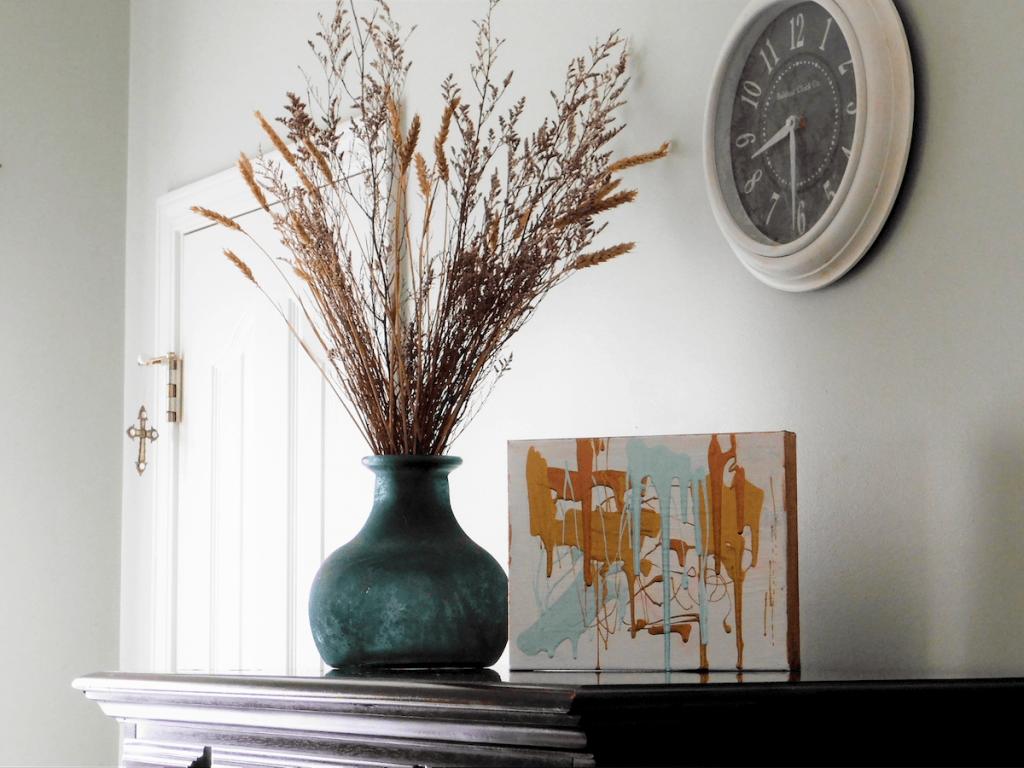 Accessories on top of dresser flower vase and orange drip art