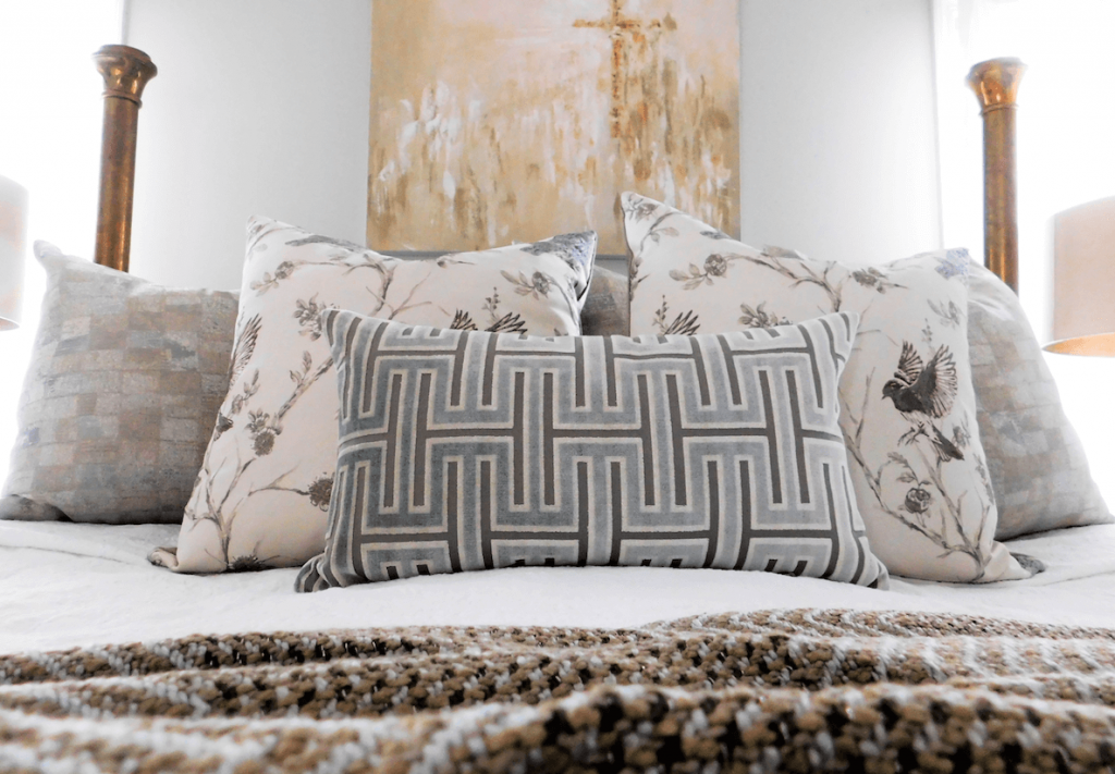 Close up of new bedding, pillows, throws and wall art in a redesigned room for empty nesters